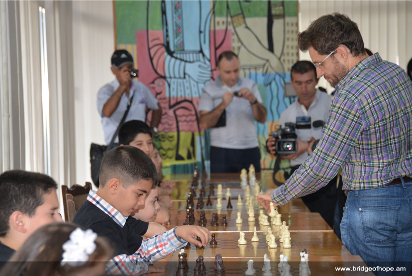 Levon Aronyan is playing chess with kids